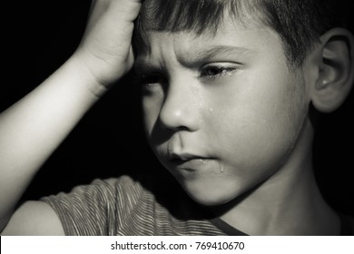 Little sad boy crying on black background. Abuse of children concept