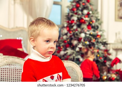 Little sad boy in a festive bedroom on the background of the Christmas tree.