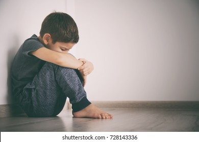 Little sad boy sitting on floor at home