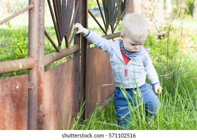 Little sad, disappointed boy walks away from a rusty closed gate