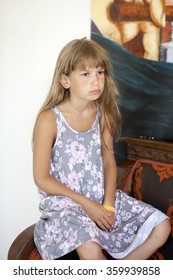 little sad girl with brown eyes sitting on chair