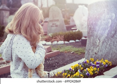 little sad girl in front of grave