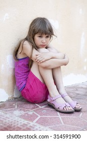 little sad girl with long hair sitting hugging her knees, leaning against the wall