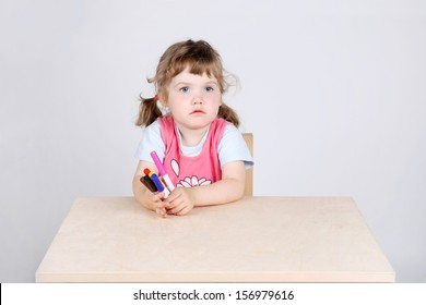 Little sad girl sits at wooden table and holds with felt-tip pens on grey background.
