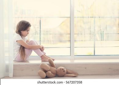 Little sad girl sitting on windowsill
