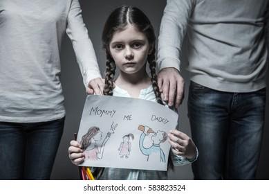 Little sad girl standing between her parents