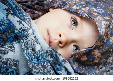 Little  sad three years old girl hidden in scarf