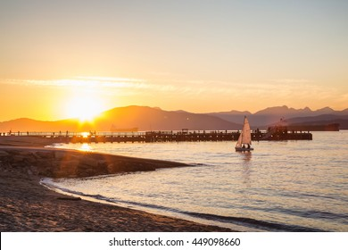 Little Sail Boat coming in to dock on shore at Jericho Beach, Vancouver, British Columbia, Canada. Taken during sunset.