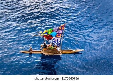 A little sailing traditional boat  canoe, colorful sails made of umbrella textile,  ocean background, Papua New Guinea, Tufi