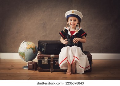 little sailor with  binoculars  sitting on travel bags with copy space , conceptual for travel