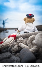 Little sailor teddy bear sit at harbor, looks toward sea, full of feelings, away from home (copy space)