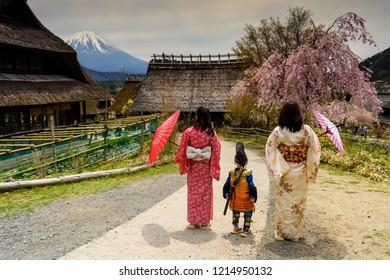 Little samurai boy with sword and Two Kimono Japanese women at Saiko Iyashi no Sato Nenba, former farming, village near Mountain Fuji, Japan. Preserved wooden thatched roof houses near lake Saiko.