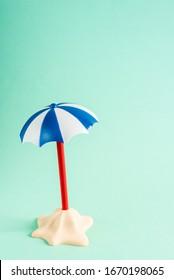 Little sand island with umbrella on pastel blue background. Minimal creative summer concept. Flat lay