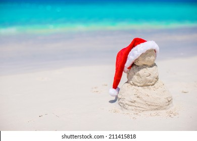 Little sandy snowman with red Santa Hat on white Caribbean beach