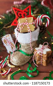 Little Santa Claus boot with christmas presents and festive decorations