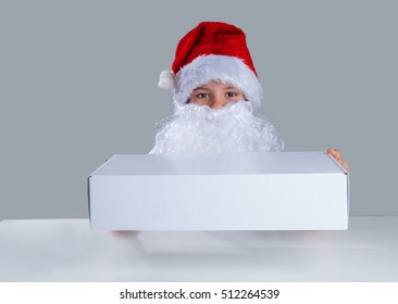 Little Santa Claus gives a white box. He is sitting at a white table. He looks into the camera. Gray background. Close-up.