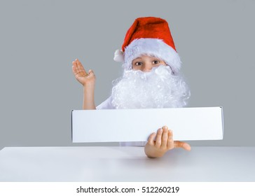 Little Santa Claus holding in his left hand a white box, right hand held up. He is sitting at a white table. He looks into the camera. Gray background. Close-up.