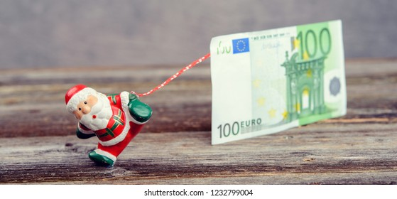 little Santa Claus pulling big euro banknote