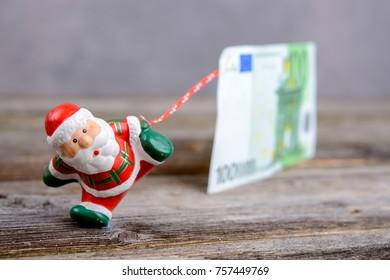 little Santa Claus pulling big euro banknote