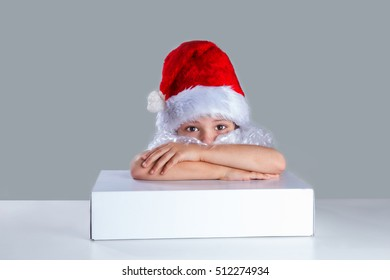 Little Santa Claus put his head on his folded arms on the white box. He is sitting at a white table. Sad looking at the camera. Gray background. Close-up.
