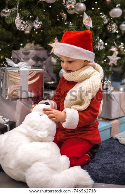 Pequeño Santa se sienta al lado de un árbol de Navidad con oso de peluche blanco