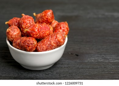 Little sausages in a bowl on a black wooden table