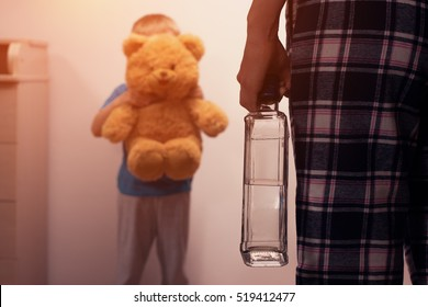 Little scared son covering his face with toy bear from angry drunk mother. Child abuse. Alcoholic addiction. Domestic violence.