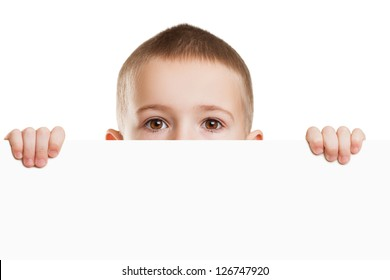 Little scared or worried child boy holding blank white sign or placard hiding face