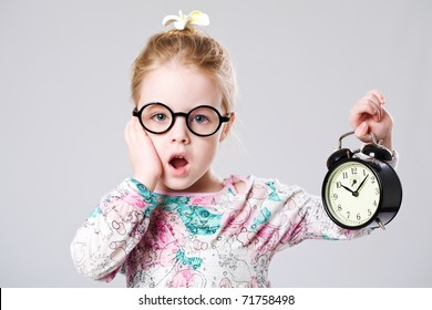 Little scary girl holding a clock