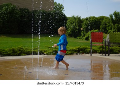 Little School Aged Caucasian Blond Boy in Red White and Blue Bathing Swim Suit Playing Outside With Scrunched Face Running Through Water at Splash Pad with Beach Patio Chairs and Green Leaf Background