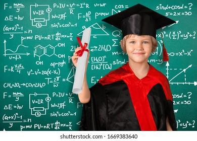 Little school boy in a classroom on blackboard background