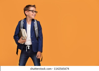 Little school boy in eyeglasses with backpack standing over orange background, holding books, smiling.