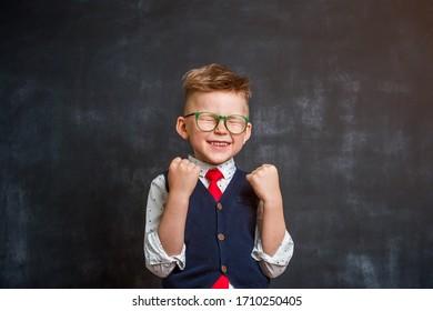 Little school boy so happy and luck. Back to school. Kid isolated on chalkboard.