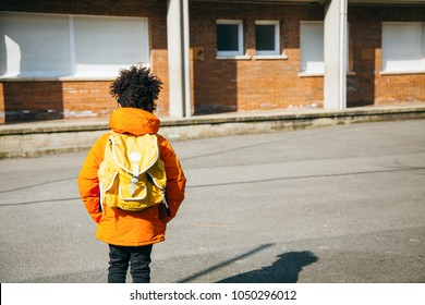 Little school boy in orange coat walking at the entrance of the school with a yellow backpack. Back view