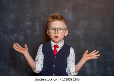 Little school boy with raised hands