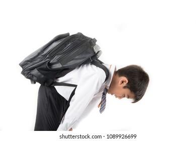 Little school boy taking heavy bag full of books on his back