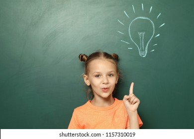 Little school child near chalkboard with lightbulb drawing