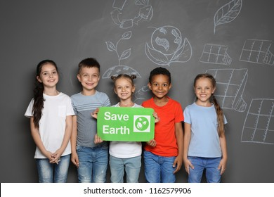 Little school children with placard SAVE EARTH and drawings on grey background