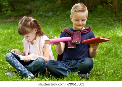 Little school children read a book in nature. Smart little pupil. Early development of children. Training and rest