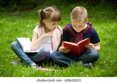 Little school children read a book in nature. Smart little pupil. Early development of children. Training and rest