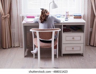 Little school girl doing homework in her room, view from the back