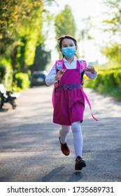 Niña de la escuela vuelve a la escuela después de un brote de pandemia con máscara