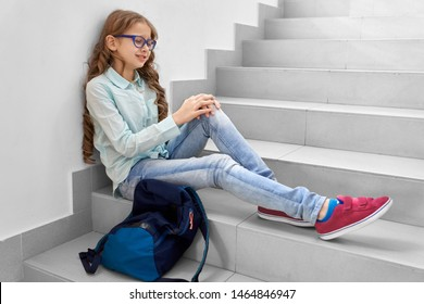 Little school girl leaning to wall , sitting on stairs of corridor and crying, near backpack. Pretty blonde girl in eyeglasses have sad mood, offended by her classmates. Concept of studying in school.