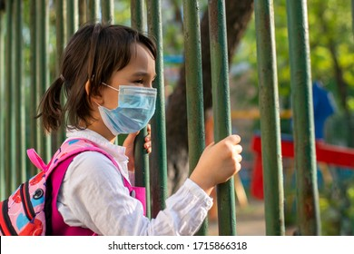 Little school girl sitting next to school fence waiting for going back to clases after pandemic outbreak