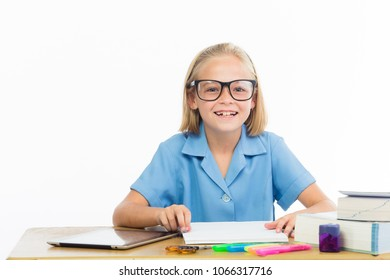 Little school girl wearing glasses sitting infront of her school books.