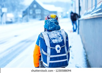 Little school kid boy of elementary class walking to school during snowfall. Early morning and snowy streets in city. Student with backpack or satchel in colorful winter clothes