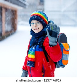 Little school kid boy of elementary class walking to school during snowfall. Happy child having fun and playing with first snow. Student with eye glasses backpack in colorful winter clothes