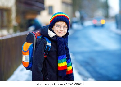 Little school kid boy of elementary class walking to school during snowfall. Happy healthy child with glasses having fun and playing with snow. With backpack or satchel in colorful winter clothes.