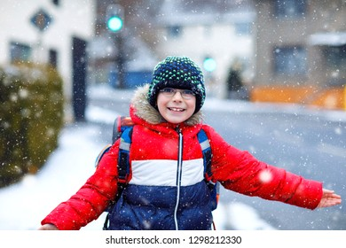 Little school kid boy of elementary class walking to school during snowfall. Happy child having fun and playing with first snow. Student with eye glasses backpack in colorful winter clothes.