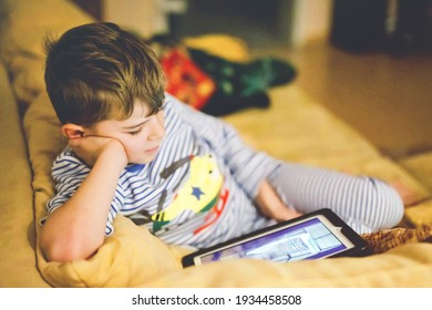 Little school kid boy making homework with tablet. Schoolchild reading and learning with computer, searching for information in internet and looking cartoons beforte sleeping and going to bed.